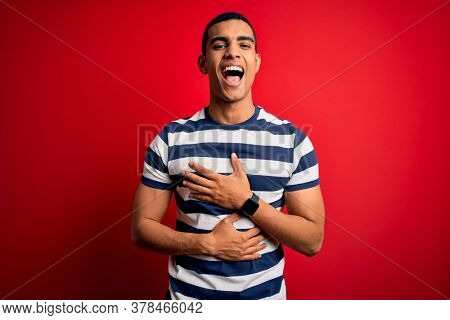 Handsome african american man wearing casual striped t-shirt standing over red background smiling and laughing hard out loud because funny crazy joke with hands on body.