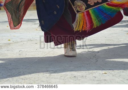A Monk Is Performing A Dance In A Buddhist Temple In Ladakh, India. Only His Foot , Shadow And The B