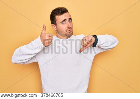 Young handsome man with blue eyes wearing casual sweater standing over yellow background Doing thumbs up and down, disagreement and agreement expression. Crazy conflict
