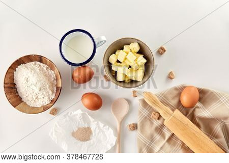 cooking food and culinary concept - rolling pin, butter, eggs, flour and cane sugar on table