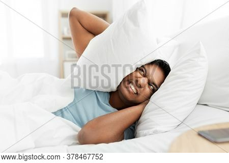 people, bedtime and rest concept - annoyed indian man lying in bed at home and covering ears with pillow
