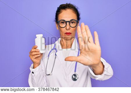 Middle age senior professional doctor woman holding pharmaceutical pills with open hand doing stop sign with serious and confident expression, defense gesture