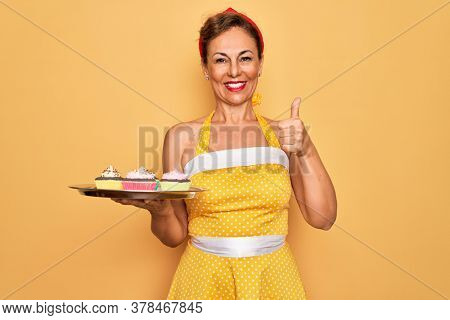 Middle age senior pin up woman wearing 50s style retro dress holding tray with cupcakes happy with big smile doing ok sign, thumb up with fingers, excellent sign