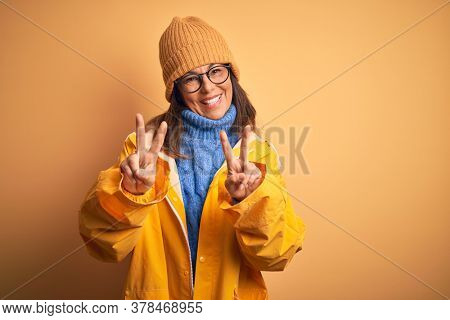 Middle age woman wearing yellow raincoat and winter hat over isolated background smiling looking to the camera showing fingers doing victory sign. Number two.