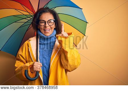 Middle age woman wearing yellow raincoat under colorful umbrella over isolated background surprised with an idea or question pointing finger with happy face, number one
