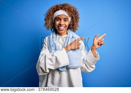 Young african american sportswoman doing sport wearing sportswear and towel smiling and looking at the camera pointing with two hands and fingers to the side.