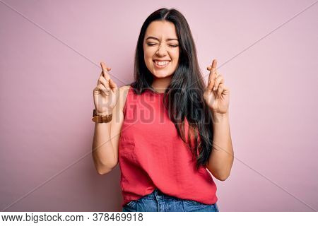 Young brunette woman wearing casual summer shirt over pink isolated background gesturing finger crossed smiling with hope and eyes closed. Luck and superstitious concept.