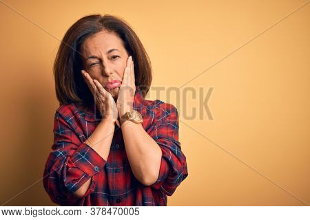 Middle age beautiful woman wearing casual shirt standing over isolated yellow background Tired hands covering face, depression and sadness, upset and irritated for problem