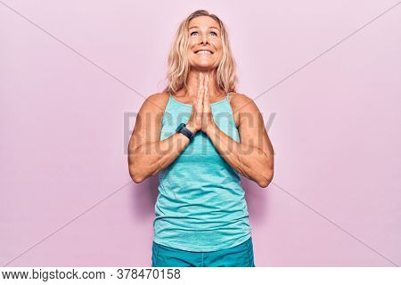 Middle age caucasian blonde woman wearing sports clothes over pink background begging and praying with hands together with hope expression on face very emotional and worried. begging.