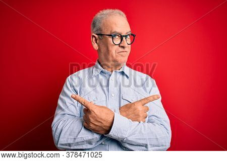 Middle age handsome hoary man wearing casual striped shirt and glasses over red background Pointing to both sides with fingers, different direction disagree