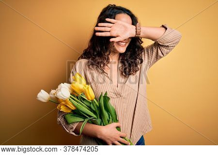 Young beautiful romantic woman with curly hair holding bouquet of yellow tulips Smiling cheerful playing peek a boo with hands showing face. Surprised and exited