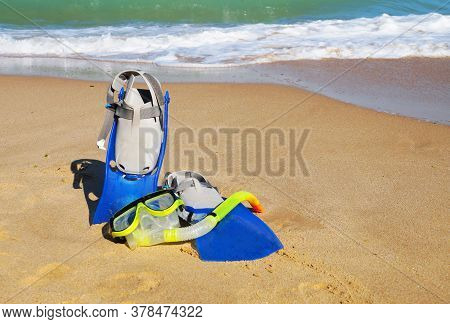 Flippers And Mask For Swimming On The Sand Against The Background Of The Sea And Clear Sky