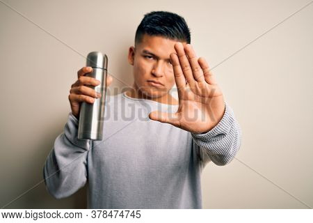 Young handsome latin man holding thermo with water over isolated white background with open hand doing stop sign with serious and confident expression, defense gesture