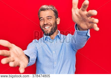 Young handsome blond man wearing casual shirt standing over isolated red background looking at the camera smiling with open arms for hug. Cheerful expression embracing happiness.