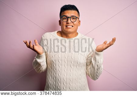 Young handsome latin man wearing white casual sweater and glasses over pink background clueless and confused expression with arms and hands raised. Doubt concept.