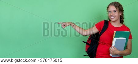 German Female Student With Red Shirt Pointing Sideways With Copy Space Isolated On Green Background