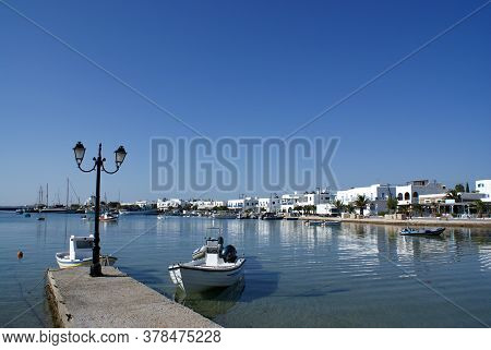 The Charming Greek Island Of Antiparos. A Small Boat Moored In The Calm Waters Of The Islands Pictur