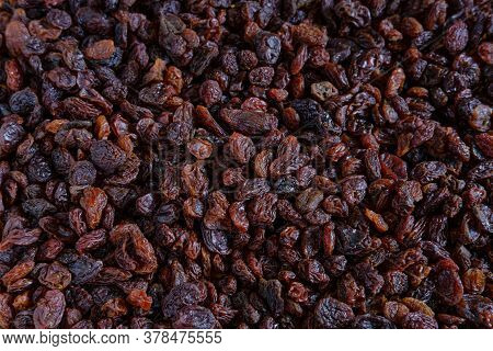 Background Of Dark, Bright And Large Raisins Scattered On The Table.