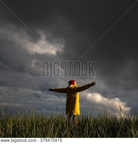 Man In Yellow Raincoat And Red Hat With Spreading Hands Wide Open Standing On The Field In Rainy Wea