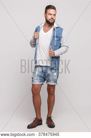 Stylish Young Cheerful Guy With A Beautiful Beard In A Denim Jacket, A White T-shirt And Denim Short