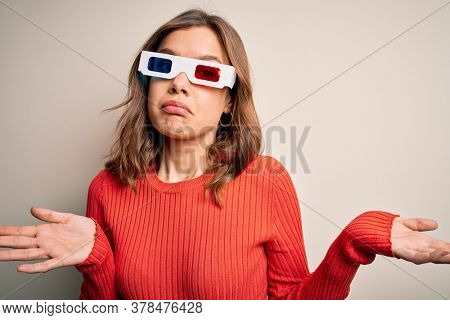 Young blonde girl wearing 3d cinema glasses over isolated background clueless and confused expression with arms and hands raised. Doubt concept.