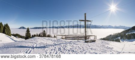 Summit Cross On Snow Mountain With Blue Sky And Sun. Great View To Mountain Range Above Inversion Va