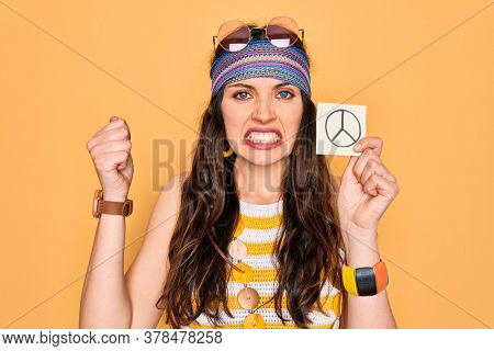 Beautiful hippie woman with blue eyes wearing sunnglasses holding peace symbol reminder annoyed and frustrated shouting with anger, crazy and yelling with raised hand, anger concept