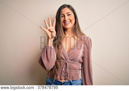 Young beautiful brunette elegant woman with long hair standing over isolated background showing and pointing up with fingers number four while smiling confident and happy.