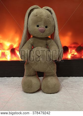 Plush Beige Bunny On The Background Of The Fireplace.