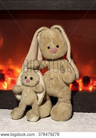 Family Of Rabbits Near The Fireplace. Soft Toys Of Bunnies.