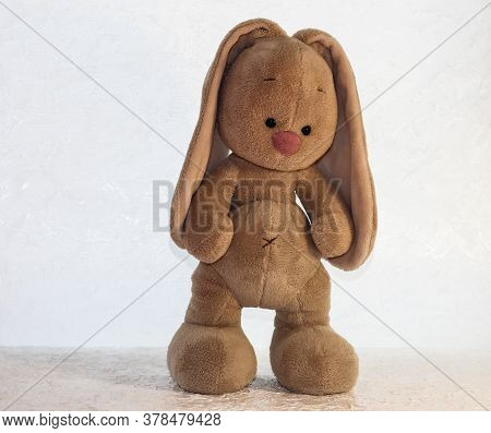 A Fluffy Hare On A Light Background. Toy Rabbit.