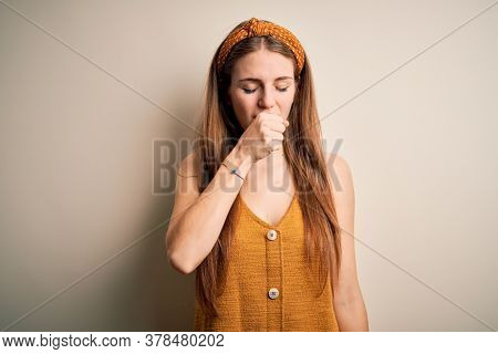 Young beautiful redhead woman wearing casual t-shirt and diadem over yellow background feeling unwell and coughing as symptom for cold or bronchitis. Health care concept.