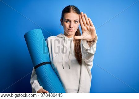 Young beautiful redhead sporty woman doing sport holding yoga mat over blue background with open hand doing stop sign with serious and confident expression, defense gesture