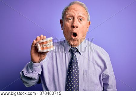 Grey haired senior man holding orthodontic prosthesis denture over purple background scared in shock with a surprise face, afraid and excited with fear expression