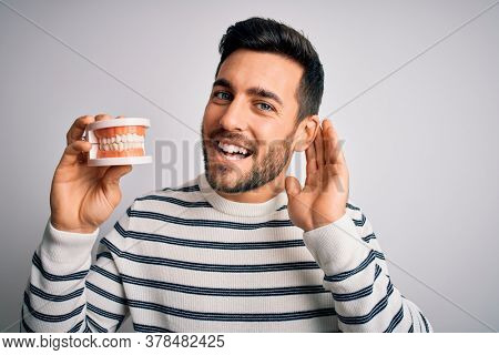Young handsome man with beard holding plastic denture teeth over white background smiling with hand over ear listening an hearing to rumor or gossip. Deafness concept.