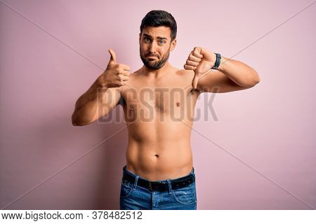 Young handsome strong man with beard shirtless standing over isolated pink background Doing thumbs up and down, disagreement and agreement expression. Crazy conflict