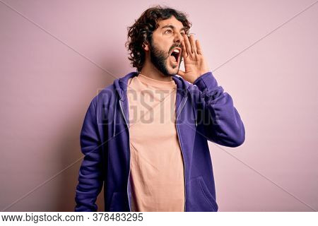 Young handsome sporty man with beard wearing casual sweatshirt over pink background shouting and screaming loud to side with hand on mouth. Communication concept.