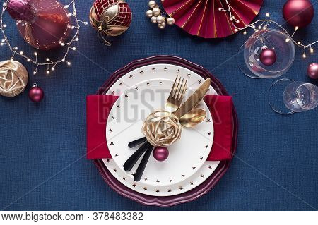 Christmas Table Setup With Golden Utensils, Red Deco. Flat Lay On Classic Blue Linen Textile Table.