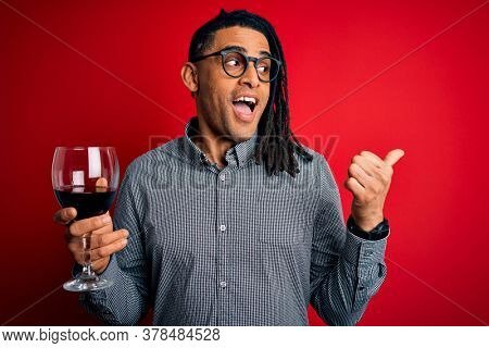 Young african american afro sommelier man with dreadlocks drinking glass of wine pointing and showing with thumb up to the side with happy face smiling