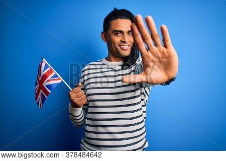 Young african american patriotic man with dreadlocks holding united kingdom flag with open hand doing stop sign with serious and confident expression, defense gesture