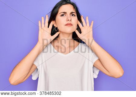 Young beautiful brunette woman wearing casual white t-shirt over purple background Trying to hear both hands on ear gesture, curious for gossip. Hearing problem, deaf