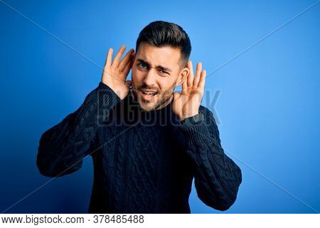 Young handsome man wearing casual sweater standing over isolated blue background Trying to hear both hands on ear gesture, curious for gossip. Hearing problem, deaf