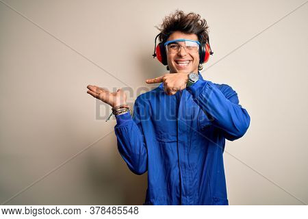 Young constructor man wearing uniform and earmuffs over isolated white background amazed and smiling to the camera while presenting with hand and pointing with finger.