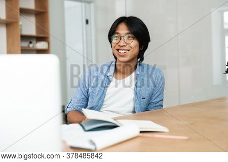 Image of young asian smiling man in eyeglasses working with laptop while sitting at table in office