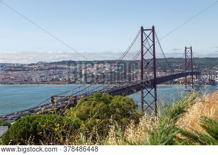 Bridge On April 25 In Lisbon On The Tejo River With Moving Cars. A Sunny Day And A View Of A Modern