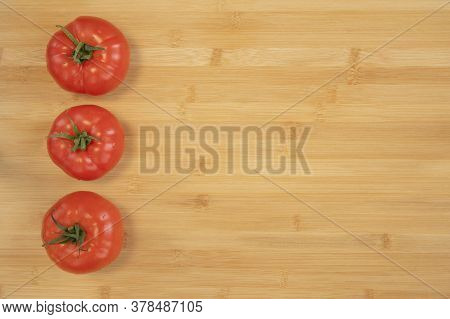 Fresh Tomatoes On Bamboo Wooden Background With Copy Space