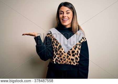 Young beautiful woman wearing casual sweatshirt standing over isolated white background smiling cheerful presenting and pointing with palm of hand looking at the camera.