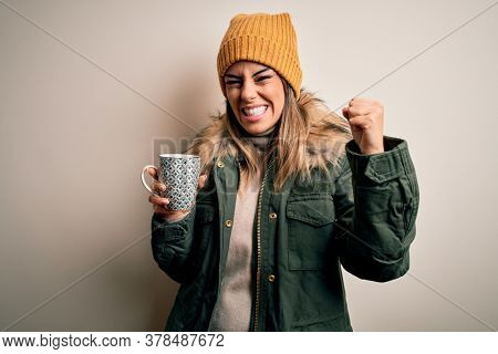 Young beautiful brunette woman wearing snow clothes drinking mug of coffee annoyed and frustrated shouting with anger, crazy and yelling with raised hand, anger concept