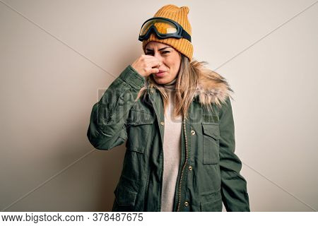 Young brunette skier woman wearing snow clothes and ski goggles over white background smelling something stinky and disgusting, intolerable smell, holding breath with fingers on nose. Bad smell