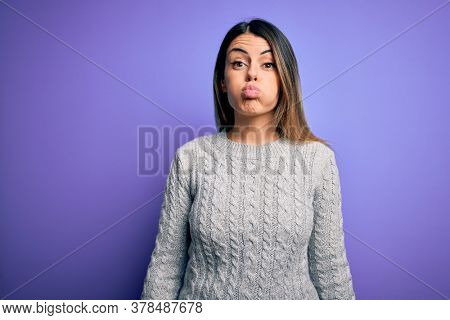 Young beautiful woman wearing casual sweater standing over isolated purple background puffing cheeks with funny face. Mouth inflated with air, crazy expression.